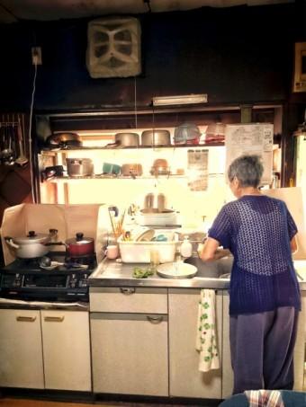 写真AC 台所に立つおばあさん